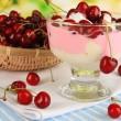 Delicious cherry dessert in glass vase on wooden table on natural background — Stock Photo
