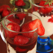 Delicious strawberry desserts in glass vase on wooden table close-up — Stock Photo