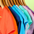 Variety of casual shirts on wooden hangers,on blue background — Stock Photo #27107347
