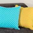 Colorful pillows on couch isolated on white — Stock Photo #27107465