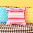 Colorful pillows on couch on yellow background — Stock Photo #27107473