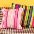 Colorful pillows on couch on yellow background — Stock Photo #27107475