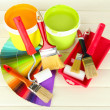 Set for painting: paint pots, brushes, paint-roller on white wooden table — Stok fotoğraf