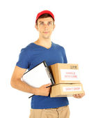 Young delivery man holding parcels and clipboard, isolated on white — Stock Photo