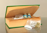 Narcotics in book-hiding place on gray background — Stock Photo