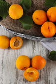 Apricots in basket on wooden table — Stock Photo
