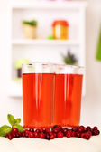 Glasses of cranberry juice and ripe red cranberries on table — Stock Photo