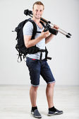 Handsome photographer with camera and tripod, on gray background — Stock Photo