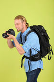 Handsome photographer with camera, on green background — Stock Photo