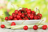 Cherry berries on plate on wooden table on bright background — Stock Photo