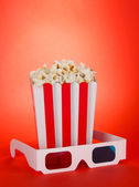 Popcorn and 3D glasses on red background — Stock Photo