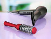 Hair dryer and comb brush, on table in beauty salon — Stock Photo