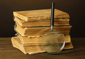 Magnifying glass and books on brown background — Stock Photo