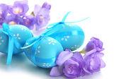 Ok ve çiçekler, üzerinde beyaz izole parlak paskalya yumurtaları — Stok fotoğraf