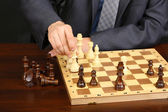 Young business man playing chess on black background — Stock Photo