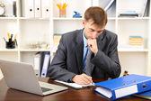 Jonge zakenman in kantoor op zijn werkplek — Stockfoto