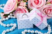 Rose och förlovningsring på blå duk — Stockfoto