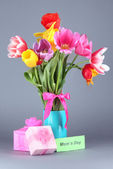 Piękne tulipany w bukiet z darów i uwaga na szarym tle — Zdjęcie stockowe