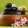 Spa stones and flowers on bamboo background — Stock Photo