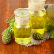Bottles of fir tree oil and green cones on wooden background — Stock Photo #27113255