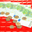 Euro banknotes and euro cents on red background — Foto de Stock