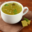 Cup of soup with bouillon cubes on wooden background — Stock Photo