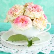 Roses in cup on napkin on blue background — Stok fotoğraf