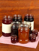 Tasty jam in banks on wooden background — Stock Photo