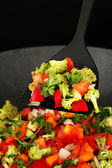 Vegetable ragout in wok, isolated on black — Stock Photo