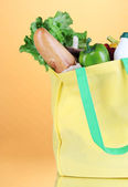 Eco bag with shopping on orange background — Stock Photo