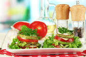 Tasty roasted marrow and tomato slices with salad leaves, on bright background — Stock Photo