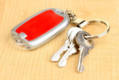 House keys and keychain on wooden background — Stock Photo