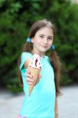 Little girl skates eating tasty ice-cream at park background — Stock Photo