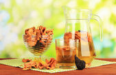 Assorted dried fruits in vase and compote of dried fruits on wooden table on natural background — Stock Photo