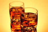 Brandy glasses with ice on yellow background — Stock Photo