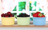 Ripe mulberries with cherry and strawberries in bowls on table in room — Stock Photo