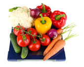 Fresh vegetables on scales on grey background — Stock Photo