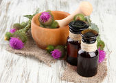 Medicine bottles and mortar with thistle flowers on wooden background — Stock Photo