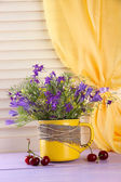 Beautiful bouquet of wildflowers in cup and berries on wooden table — Stock Photo