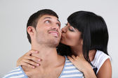 Bella coppia di innamorati baciare su sfondo grigio — Foto Stock
