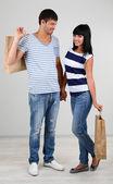 Bella coppia di innamorati è lo shopping su sfondo grigio — Foto Stock