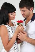 Beautiful loving couple with rose on grey background — Stock Photo