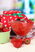 Homemade strawberry jam, on napkin, on color wooden table, on bright background — Stock Photo