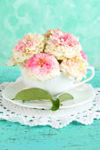 Roses in cup on napkin on blue background — ストック写真