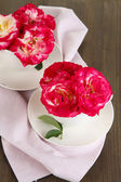 Roses in cups on napkin on wooden background — Stock Photo