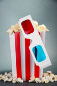 Popcorn and 3D glasses on grey background — ストック写真