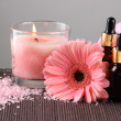 Beautiful pink candle with flower and towel on bamboo mat — Stock Photo