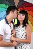 Beau couple d'amoureux avec parapluie sur fond gris — Photo