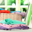 Steam iron and wicker basket with clothes, on bright background — Foto Stock