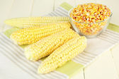 Fresh and dried corn on wooden background — Stock Photo